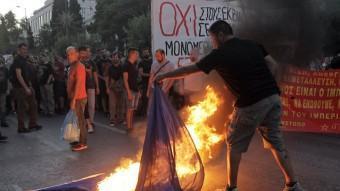 Un grup d'activistes d'esquerres cremant una bandera de la UE al centre d'Atenes. EFE