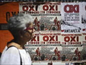 Una dona camina davant d'uns cartells que demanen el vot negatiu al referèndum de la setmana passada.  ARXIU /EFE