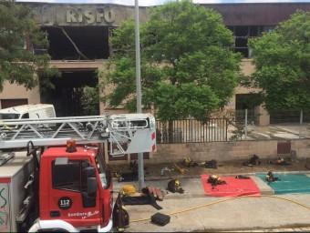 Els bombers vigilaven ahir a migdia que no revifés l'incendi que va cremar l'empresa Ris Fort R.M.B