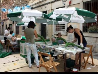 Uns para-sols ajuden a protegir de la calor unes veïnes del carrer Fraternitat a l'hora de completar les decoracions per la festa major de Gràcia ACN