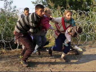 Diversos refugiats, dos d'ells menors, travessen la frontera de filferro per entrar a Hongria REUTERS
