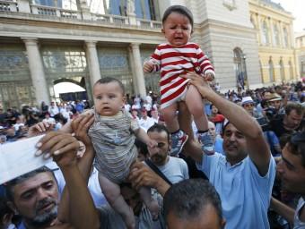 Refugiats aixecant els seus fills i mostrant bitllets de tren, ahir a l'exterior de l'estació de l'est de Budapest REUTERS / Laszlo Balogh