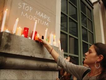 Una noia col·loca una espelma davant d'una pintada on es llegeix Stop Mare Mortum ACN