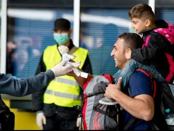 Un pare i el seu fill somriuen en rebre un peluix a l'estació de Munic, provinent de Salzburg EFE