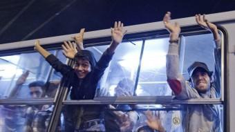 Refugiats saluden des d'un autobús a Hongria, a punt de marxar cap a Àustria.