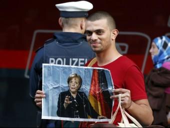 Un refugiat a l'estació de tren de Munic amb un retrat de Merkel REUTERS