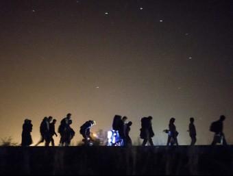 Refugiats caminant de nit a la frontera entre Sèrbia i Hongria, a Roszke aquesta matinada EFE