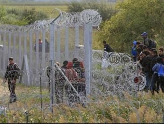 Un grup de persones s'han trobat amb la tanca de filferro vigilada per l'exèrcit hongarès que els ha impedit creuar la frontera des de Sèrbia a Röszke (Hongria) REUTERS
