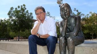 Enric Millor, cap de llista del PP, a la Plaça de la Constitució de Girona, imitant la pose de l'escultura de la nena que va néixer el mateix dia que es va aprovar la Carta Magna. MANEL LLADÓ