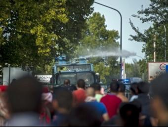 La policia hongaresa llança aigua a pressió contra els refugiats que intenten creuar la frontera des de Sèrbia, aquest dimecres al pas d'Horgos EFE