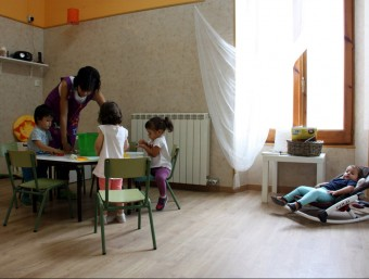 L'educadora de la llar d'infants rural de les Pallargues fent una activitat amb els nens, i a la dreta una dels petits descansant en un bressol ORIOL BOSCH / ACN