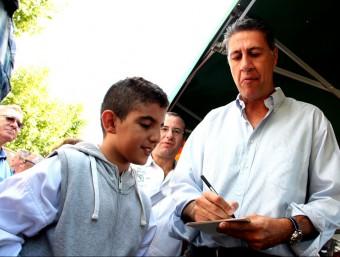 Xavier García Albiol signa un autògraf a Ahmed, un nen d'origen àrab que li ha demanat la firma fins a tres cops mentre el candidat passejava pel mercat de Cerdanyola, a Mataró ACN