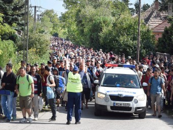 Un policia hongarès intenta dirigir una columna de desplaçats en ruta cap a Àustria, aquest dissabte a Hegyeshalom EFE