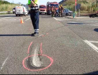 El cotxe accidentat, al fons de la imatge i els senyals a l'escenari de l'accident. ACN