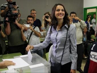 La cap de llista de C's, Inés Arrimadas, introdueix el sobre amb la papereta dins d'una urna d'un col·legi electoral del districte de les Corts, acompanyada dels seus nebots. Imatge del 27 de setembre de 2015 ACN