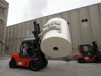Un operari trasllada un rotlle de paper de gran tonatge a la planta de Gomà-Camps a la Riba.  L'ECONÒMIC