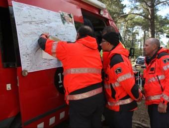 Els equips de rescat al camp base mirant el mapa de la zona on busquen el boletaire. LOURDES CASADEMONT/ ACN