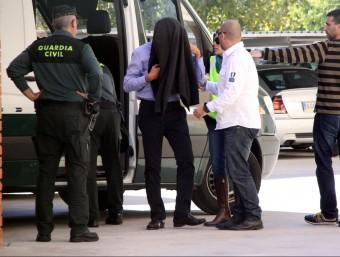 Pla general del director general d'Infraestructures, Josep Antoni Rosell, amb una jaqueta tapant-li el rostre, després d'arribar a la caserna de la Guàrdia Civil del Vendrell ACN