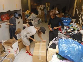 Voluntàries de l'organització Refugees Aid classificant fa uns dies en un magatzem tot el material donat per ciutadans amb l'objectiu d'ajudar les persones refugiades ORIOL DURAN