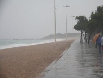 Una parella camina amb dificultats pel passeig marítim de Platja d'Aro a causa del vent i la pluja ACN