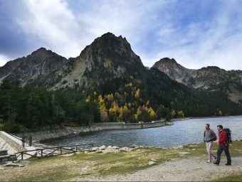 Dos excursionistes davant de l'estany de Sant Maurci, un dels llocs emblemàtics del parc nacional SANTI IGLESIAS