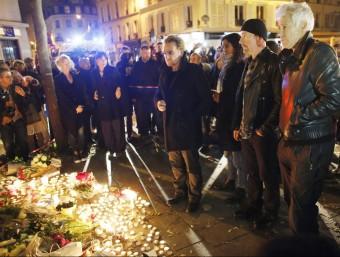 Bono, David Howell Evans i Adam Clayton, del grup U2, deixen flors en record de les víctimes dels atemptats de París, aquest dissabte a l'exterior de la sala Bataclan EFE