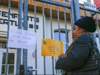 Un soldat a la Gran Place de Brussel·les, i una dona llegint el cartell d'una escola tancada per seguretat, ahir reuters