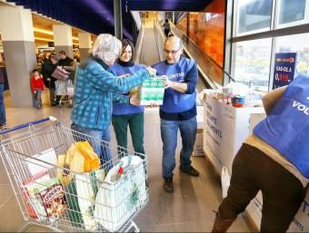 Un home dóna llet al Banc dels Aliments durant el Gran Recapte aquest dissabte a Terrassa ANDREU PUIG