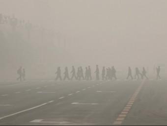 Diverses persones travessen un pas de vianants a la plaça Tiananmen, aquest dilluns a Pequin REUTERS