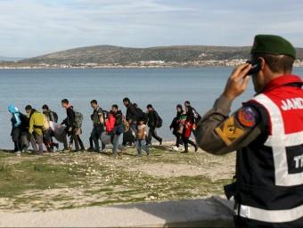 Un gendarme turc observa un grup de refugiats a la localitat de Cesme, davant l'illa grega de Quios REUTERS