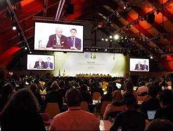 Els delegats assistents al COP21, segueixen la compareixença de Laurent Fabius, aquest dimecres a Le Bourget, als afores de París EFE