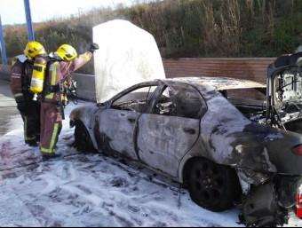 Els Bombers inspeccionen el cotxe incendiat, aquest dissabte a la sortida 12 de l'AP-7 BOMBERS DE LA GENERALITAT