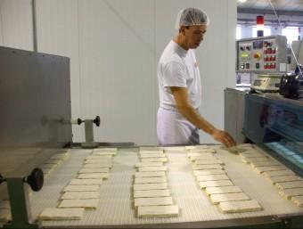 Un treballador d'una fàbrica de torrons a Xixona a la cinta on surten les barres ACN