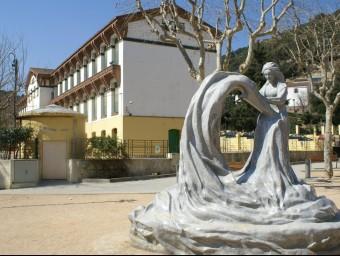 L'edifici escolar vist des d'un lateral a la plaça de Catalunya on hi ha el monument a la puntaire fet per l'escultor japonès d'Etsuro Sotoo. F. CATÀ
