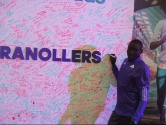 Dennis Kimetto estampa la seva signatura en mur instal·lat en la fira del corredor de la mitja marató de Granollers X.A