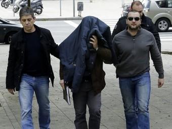 Joaquín Benítez , tapat amb la jaqueta i acompanyat de tres mossos, ahir al jutjat EFE