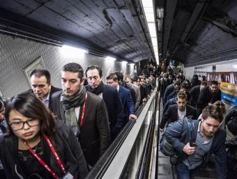 Ciutadans ahir al metro de Barcelona alguns amb la credencial del congrés de mòbils penjda del coll, sortint d'una andana JOSEP LOSADA