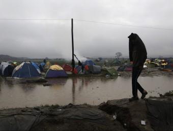 Un refugiat camina per un campament de refugiats inundat per les pluges, al costat de la frontera entre Grècia i Macedònia EFE