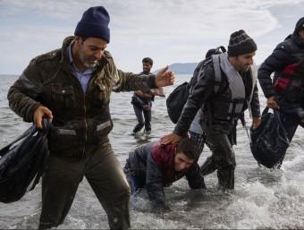 Un grup de refugiats desembarcant d'una llanxa a la costa de l'illa de Lesbos (Grècia), ahir EP