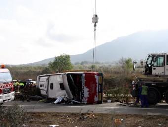Una grua aixecant l'autocar accidentat a l'AP-7 a Freginals ACN
