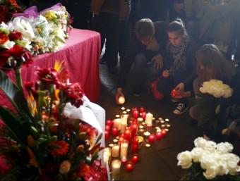 Diverses persones encenen espelmes en memòria de les víctimes de l'accident d'autocar, ahir a l'edifici històric de la UB REUTERS