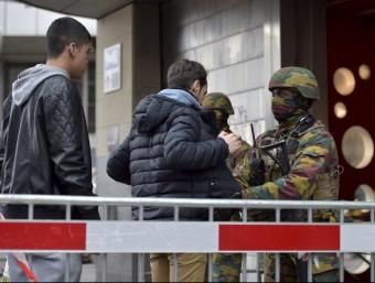 Soldats de l'exèrcit belga escorcollen uns ciutadans a l'entrada d'una estació de metro de Brussel·les