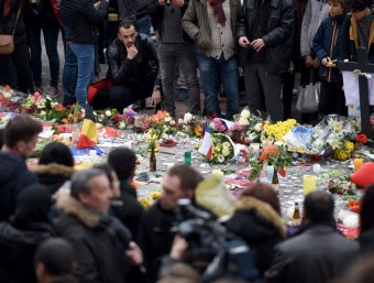 Un home observa les flors i els missatges que la gent ha deixat en homenatge a les víctimes, en una plaça de Brussel·les. AFP