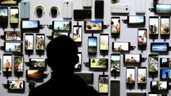 Un visitant d'una fira tecnològica mira tota la gamma de dispositius d'una coneguda marca justin sullivan / AFP