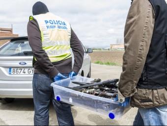 Agents dels Mossos i la Guàrdia Civil s'enduen una capsa plena d'armes blanques, aquest dimecres a El Poal EFE