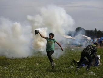 Un refugiat allunya una bomba de gasos llançada per la policia macedònia, aquest diumenge al campament d'Idomeni