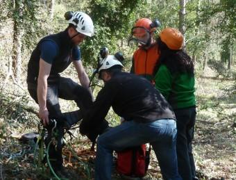 Un formador del Centre de Formació Forestal Especialitzada es col·loca els arnesos en una classe de trepa A. A