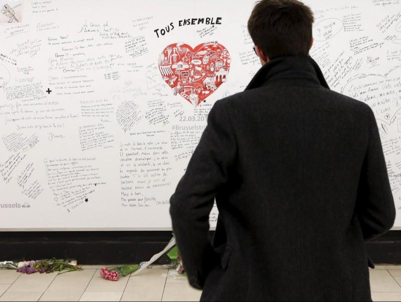 Un passatger observa el mural en homenatge a les víctimes dels atemptats, aquest dilluns a l'estació de metro Maelbeek de Brussel·les REUTERS