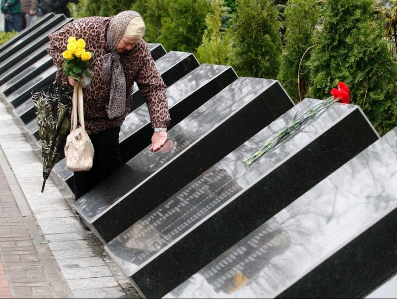 Una dona resa en un memorial de les víctimes de Txernòbil.  AFP