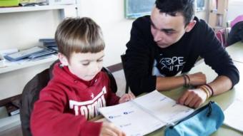 Un voluntari d'n SIE's ajudant a un alumne a fer els deures escolars CÀRITAS